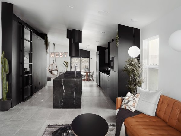 """We removed all the walls and defined the kitchen in the open space with black finishes,"" says designer Anthony W Designs. Details's all-black kitchen features a 16-foot-long marble counter and cabinetry by Lignum Cabinets."
