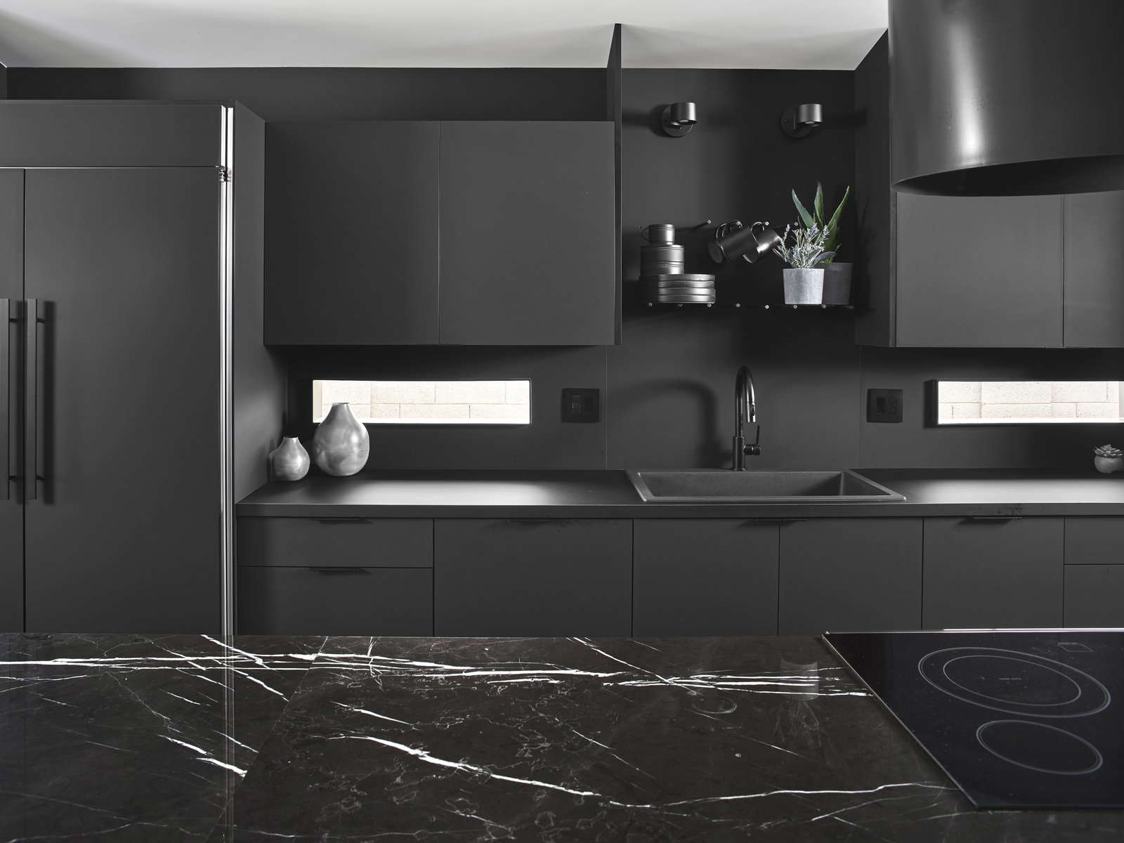 Kitchen, Laminate Counter, Drop In Sink, Laminate Cabinet, and Refrigerator The entire functional kitchen wall created by Lignum Cabinets is made from laminate, and features peg-board-like shelving above the sink allowing them to be customized to needs.  Details