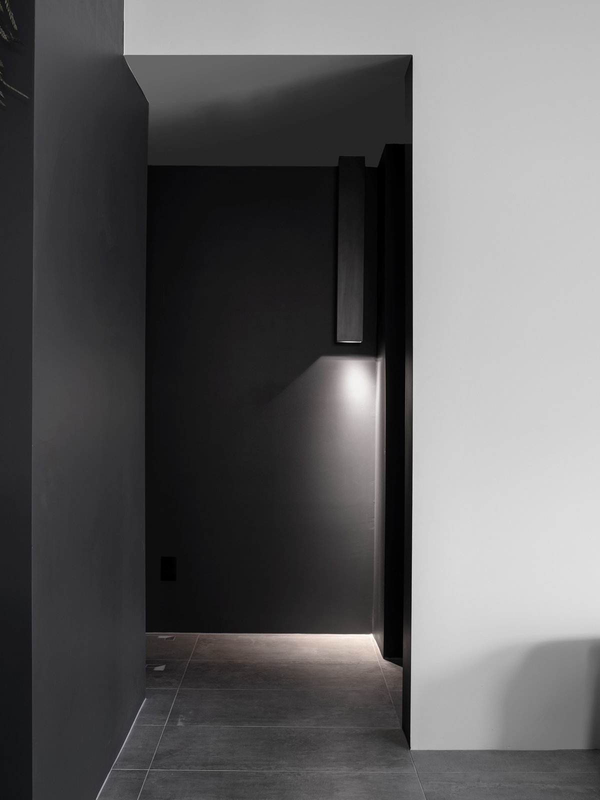 Hallway and Porcelain Tile Floor A hall light detail that discretely illuminates the floor of the black hallway.  Details