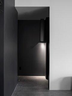 A hall light detail that discretely illuminates the floor of the black hallway.