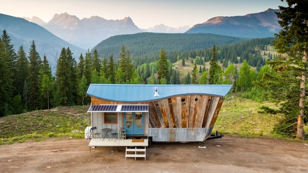 High in the Colorado mountains, this completely off-grid home cleverly fuses art and functionality. Home to a young couple and their two dogs, the eye-catching dwelling showcases the impeccable craftsmanship and creative flair of its occupants. Greg and Stephanie Parham built San Juan Tiny House to include a wavy roof, an angled front prowl, barn wood siding arranged like the rays of the sun, blue ombré shakes on the rear wall, reclaimed materials throughout, and a collapsible front porch, which features a fold-up deck and fold-down awning. On the inside, clever solutions maximize square feet and storage.