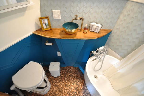 The bathroom, which features a penny-tile floor, is relatively large—and even holds a soaking tub.