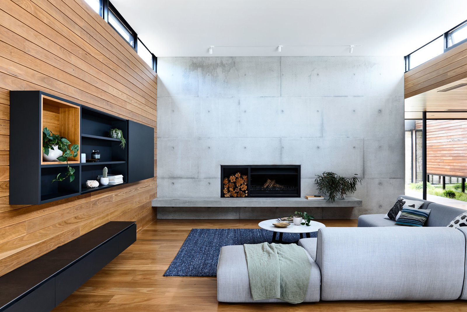 """Living Room, Sofa, Medium Hardwood Floor, Wood Burning Fireplace, and Track Lighting """"The bold concrete forms [in DS House] create a blank backdrop for the reinstatement of the indigenous landscape after bushfires...triggered a requirement for the majority of the vegetation to be removed,  DS House, Blairgowrie"""