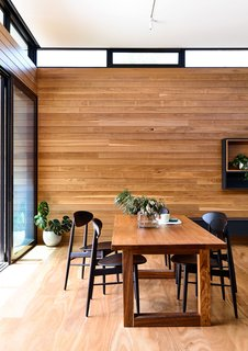The walls, floors, and ceilings of DS House are clad in timber and concrete, mirroring the style of the exterior facade. The dining room is connected to the living area by a long wooden wall.