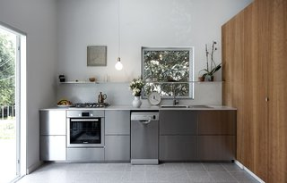 Stainless steel Ikea kitchen elevated by the cherry wood cabinetry