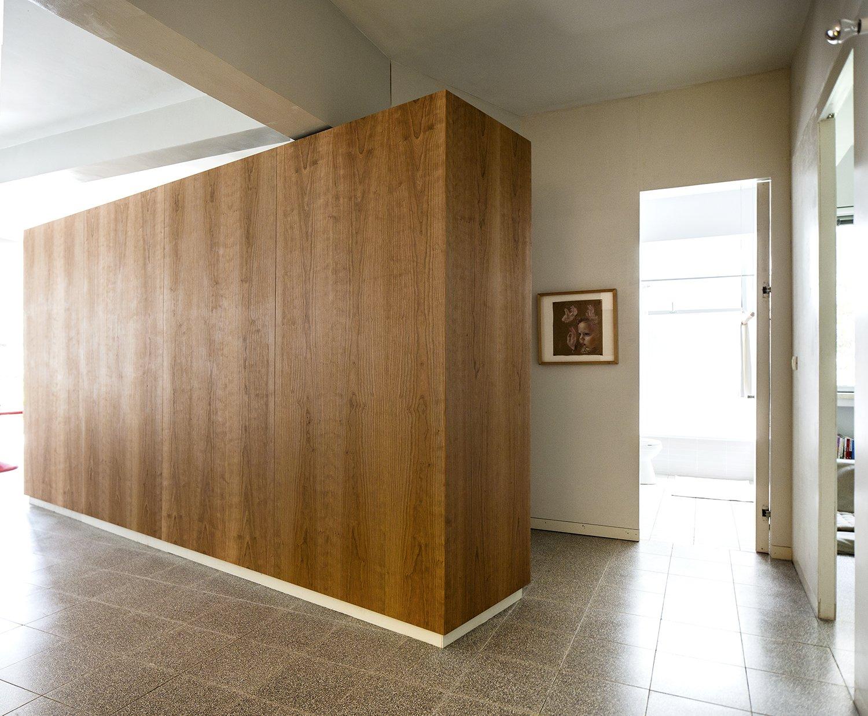 Hallway and Concrete Floor Cherry wood millwork unit as a multi purpose storage space   Nahmani Tel Aviv Apartment