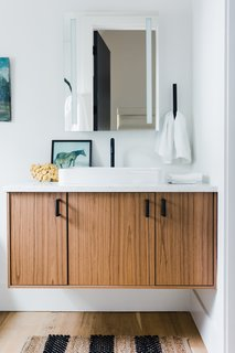 The bathrooms' white walls and wood cabinetry keep the areas light, bright, and airy.