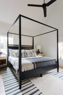 The guest bedroom houses a canopy bed with blue-and-white bedding that accentuates the sunny attached balcony where one can look out into the neighborhood, or relax and read.