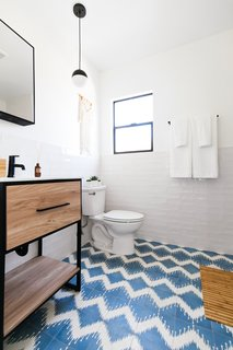 A combination of crisp white walls and funky floor tile lends big personality to this bathroom.