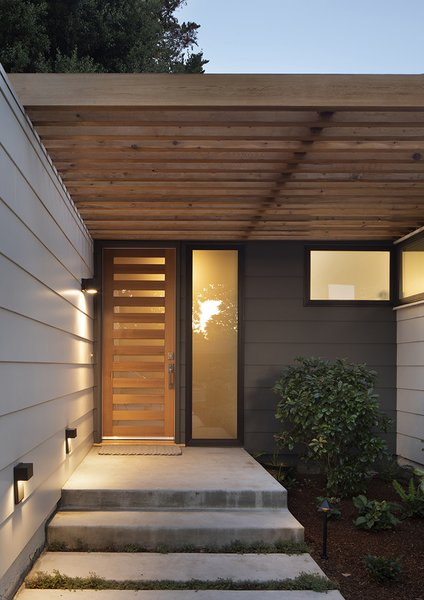 Entry way has a modern feel with custom door and lighting.