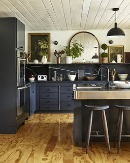 The newly renovated kitchen has soapstone countertops and a white ceiling.
