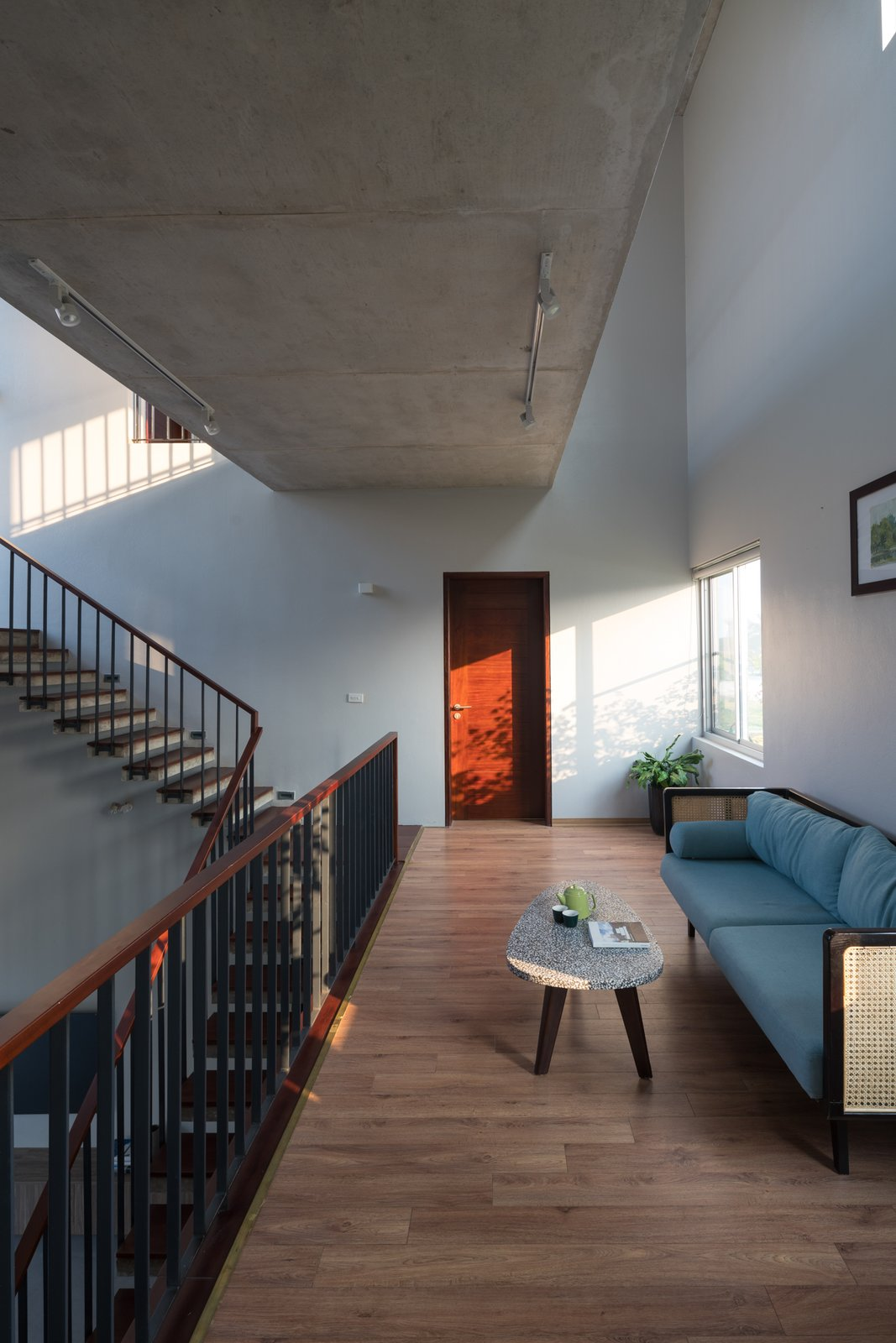 Living Room, Ceiling Lighting, Medium Hardwood Floor, Sofa, and Coffee Tables Inside, the corridors both create a space that connects people and nature, as well as the place where the daily activities of the family take place.  Ninh Binh House