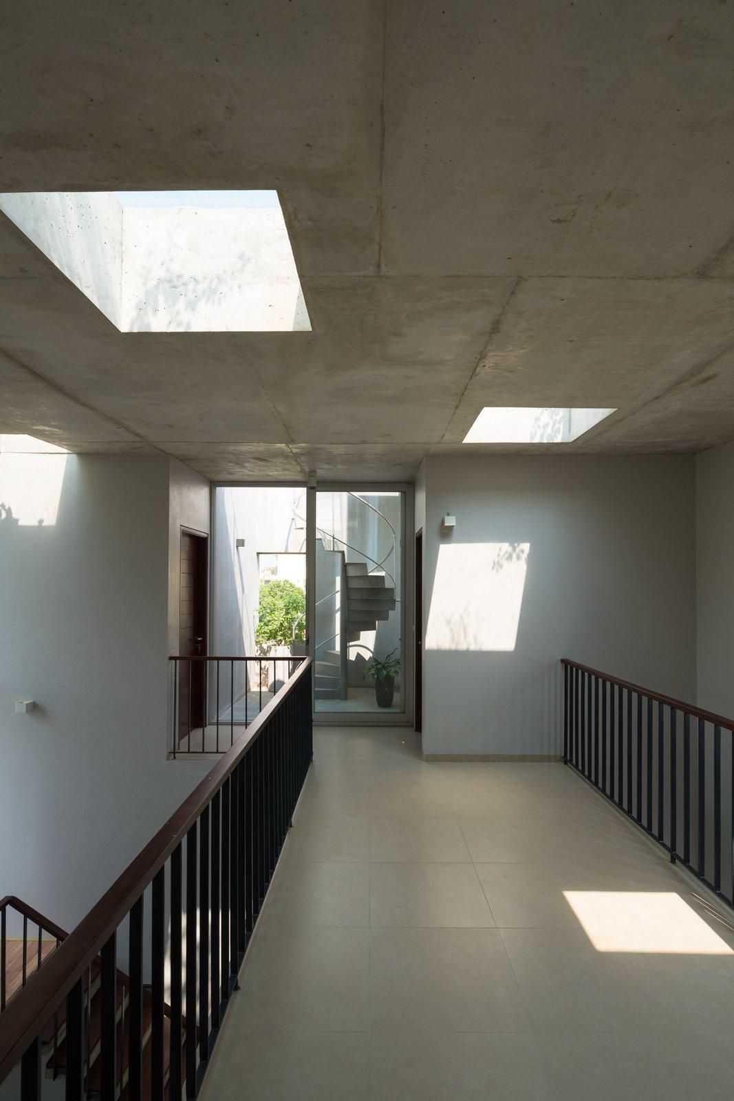 Hallway and Medium Hardwood Floor Steel stair leading to the rooftop vegetable garden.  Ninh Binh House