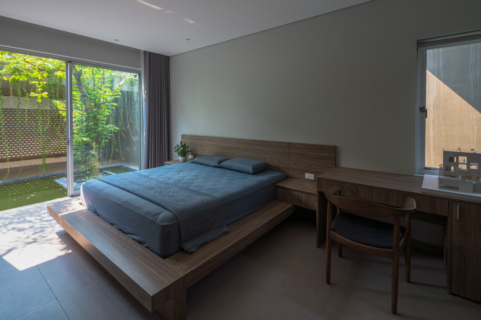Bedroom, Chair, Ceramic Tile Floor, Ceiling Lighting, and Bed Taking advantage of the natural light, ventilation and greenery, the house has a pleasant atmosphere, friendly with the environment, saving the cost of lighting and air conditioning in living.  Ninh Binh House