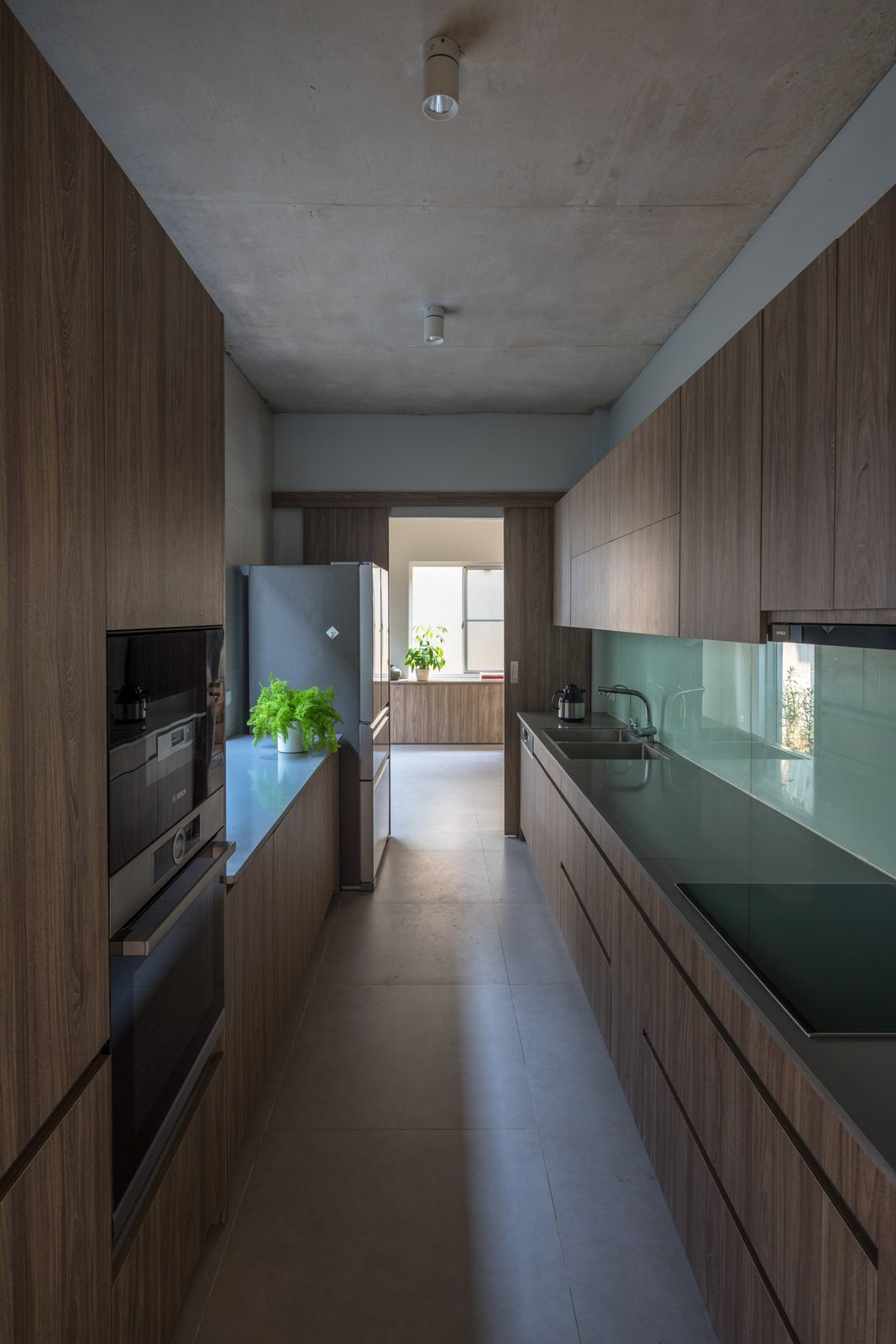 Kitchen, Ice Maker, Quartzite Counter, Dishwasher, Wood Cabinet, Microwave, Refrigerator, Ceiling Lighting, Glass Tile Backsplashe, Wall Oven, Range Hood, Cooktops, Undermount Sink, and Ceramic Tile Floor The kitchen is separated from the common living space, suitable for the needs of the family.  Ninh Binh House