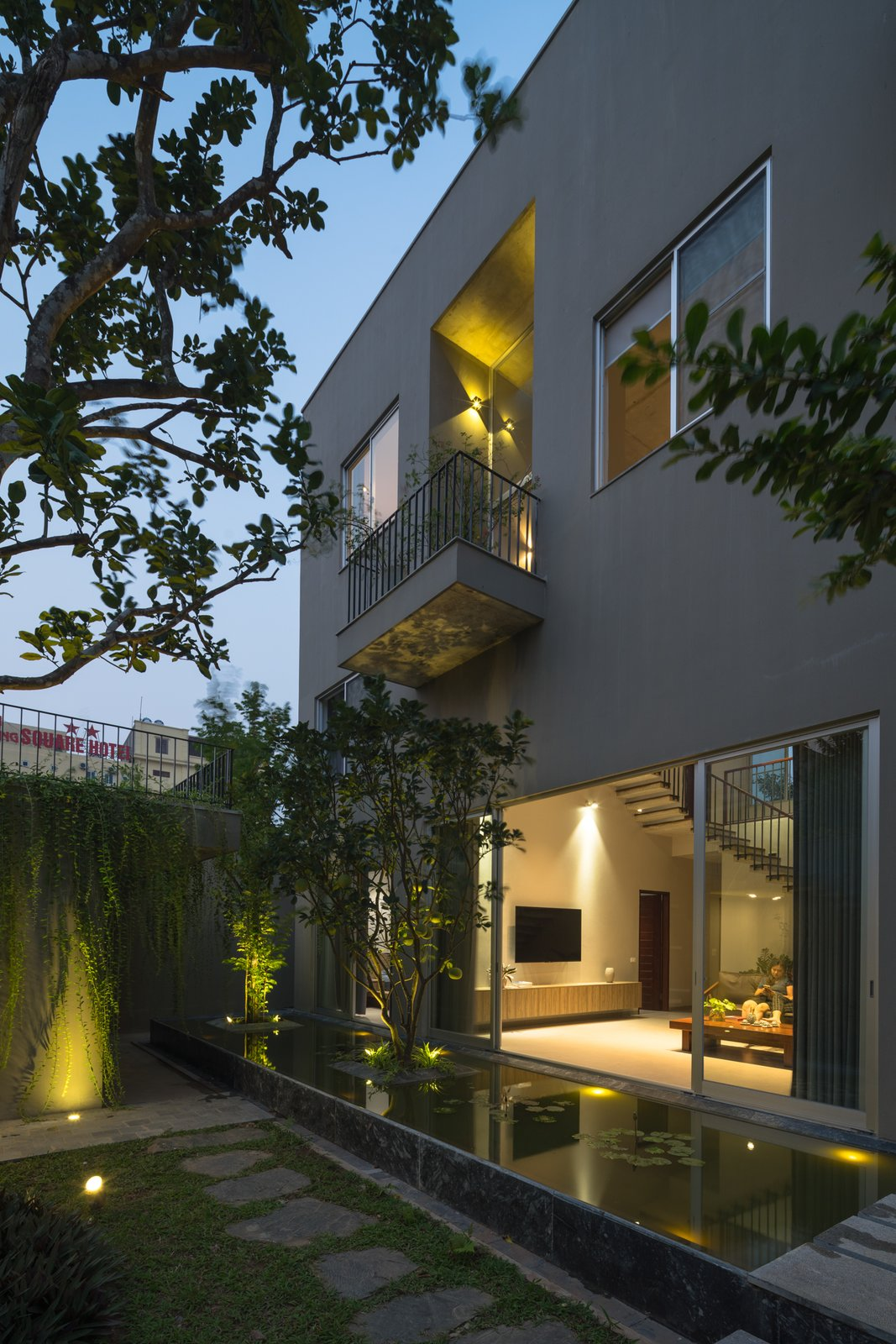 Outdoor, Small Pools, Tubs, Shower, Front Yard, Trees, Shrubs, Walkways, Grass, Concrete Fences, Wall, and Landscape Lighting The garden has become an indispensable element of the house, rather than just a decorative element as it often is in the surrounding houses.  Ninh Binh House