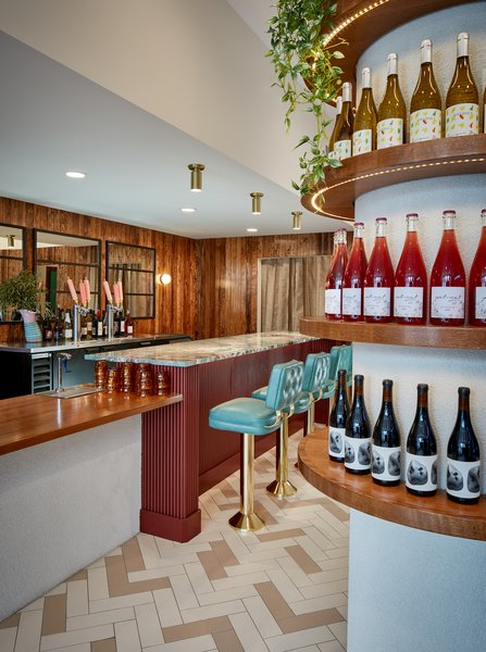 The bar, topped in Amazonite Quartzite and complemented by mirrors, wood, and seating reminiscent of a diner, is a highlight of the space.