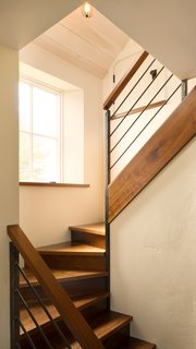 Thick slabs of walnut serve as treading on the staircase.