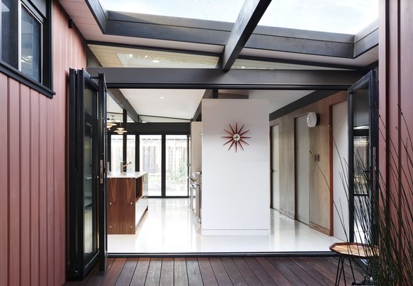 """When a custom-fabricated box beam proved too cost prohibitive, Blaine's engineer devised a steel beam strong enough to span the 18-foot length of the rear wall that didn't feel too heavy and didn't look out of place beside the original wood beams. """"Then we painted all of the structure a warm black so it becomes a feature and ties everything—new and old—together,"""" adds Blaine."""