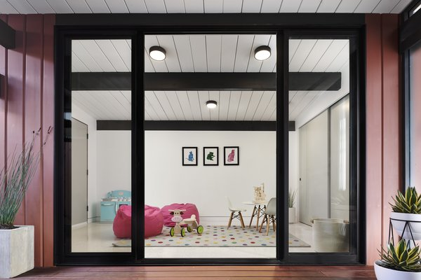 """A folding glass NanaWall system """"allows the clients to keep an eye on their kids while working in the kitchen,"""" says Blaine, who dubbed the space the 'NanAtrium.' """"It helps keep the kids safe and contained, and helps the family get back to enjoying life."""" A swing door provides easy in-and-out access when the glass wall isn't fully opened."""