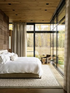 Inspiration is easily found in the earth-toned bedroom—from the trees just beyond the expansive glass.