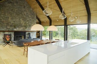 One half of the ground level comprises a fluid den, living room, dining area, and kitchen.