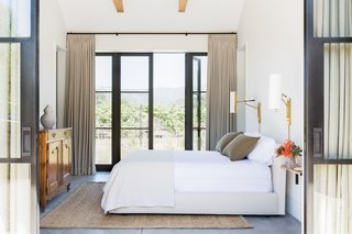 Along with antiques, the design team sourced many of the pieces throughout the home from Los Angeles showrooms and boutiques like Nickey Kehoe, Blackman Cruz, Thomas Hayes Studio, JF Chen, and for bedding and accessories, Garde. Here, a guest house bedroom directly opens onto nature.