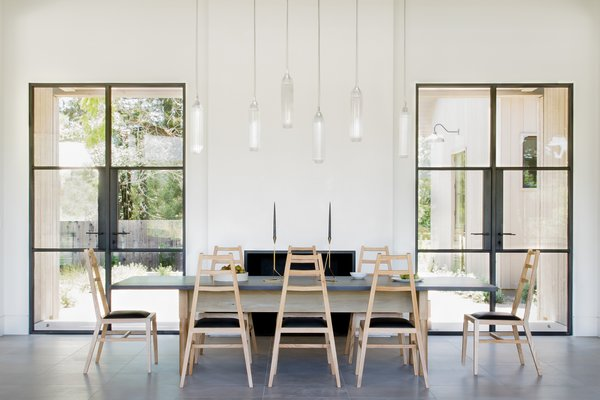 In the dining room of the main house, guests perch on black leather and bleached white oak Stahl and Band chairs around Jeff Martin Joinery's Schoolhouse table fashioned from ebonized oak and bleached and whitewashed ash. Tom Kirk Flute pendants hang overhead.