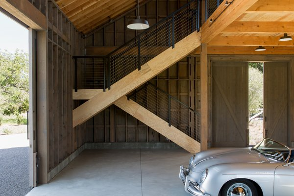 """The bi-level car barn, a spare, timber-clad structure with an A-frame roof, nods to traditional farmhouses, but is """"sleek and contemporary in spirit,"""" says Geremia. Inspired by an old photo of a porcelain farmhouse sink, it features polished concrete floors."""