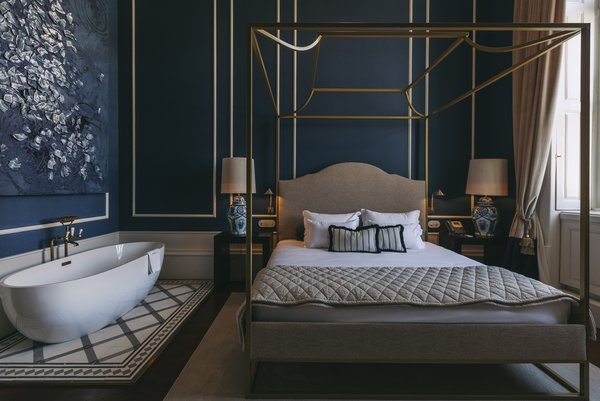 "The blue-and-white ""Porcelain"" room features a canopy bed and a mix of velvet, brass, and wood."