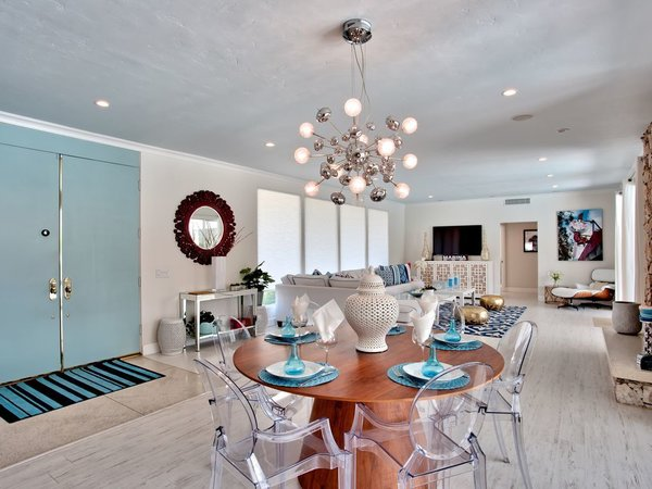 Sky blue doors open onto the intimate dining table, accentuated by transparent seating and dramatic lighting.
