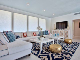 Gold poufs in the living area are among the home's post-renovation accents.