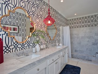 Bold wallpaper in the bathroom continues the home's vibrant character.