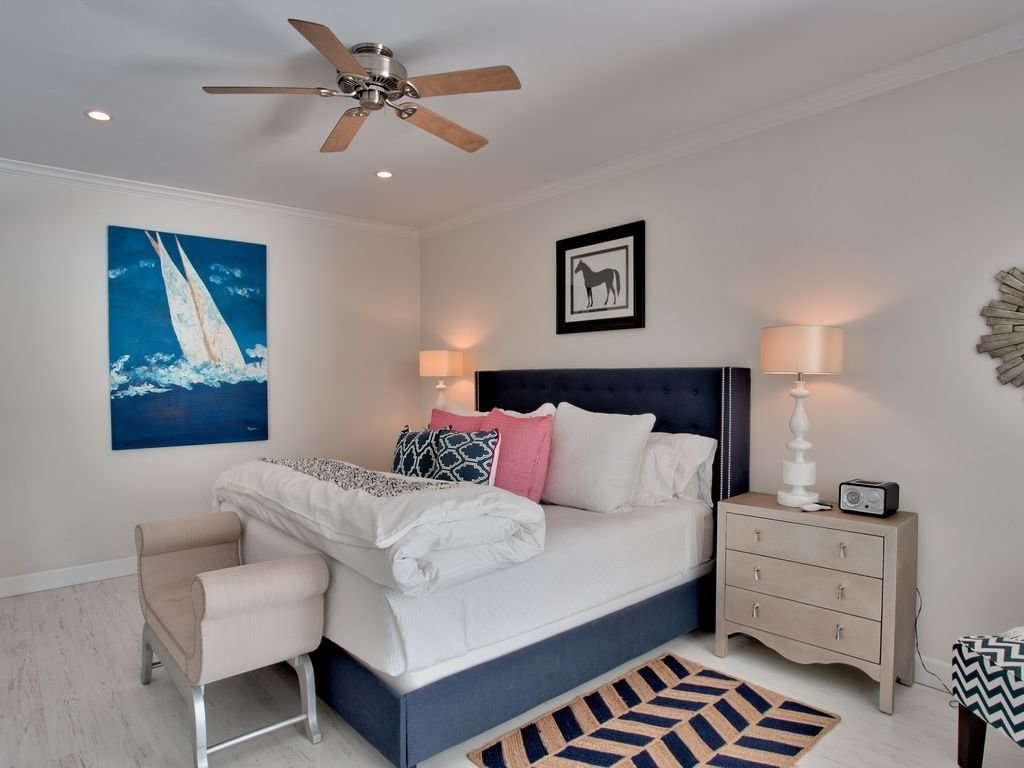 Bedroom, Lamps, Light Hardwood, Table, Recessed, Bed, Rug, Night Stands, and Bench One of the bedrooms sporting a navy-centric palette.  Best Bedroom Recessed Bench Night Stands Bed Photos from You Can Rent Lucille Ball and Desi Arnaz's Palm Springs Area Pad For $500 a Night