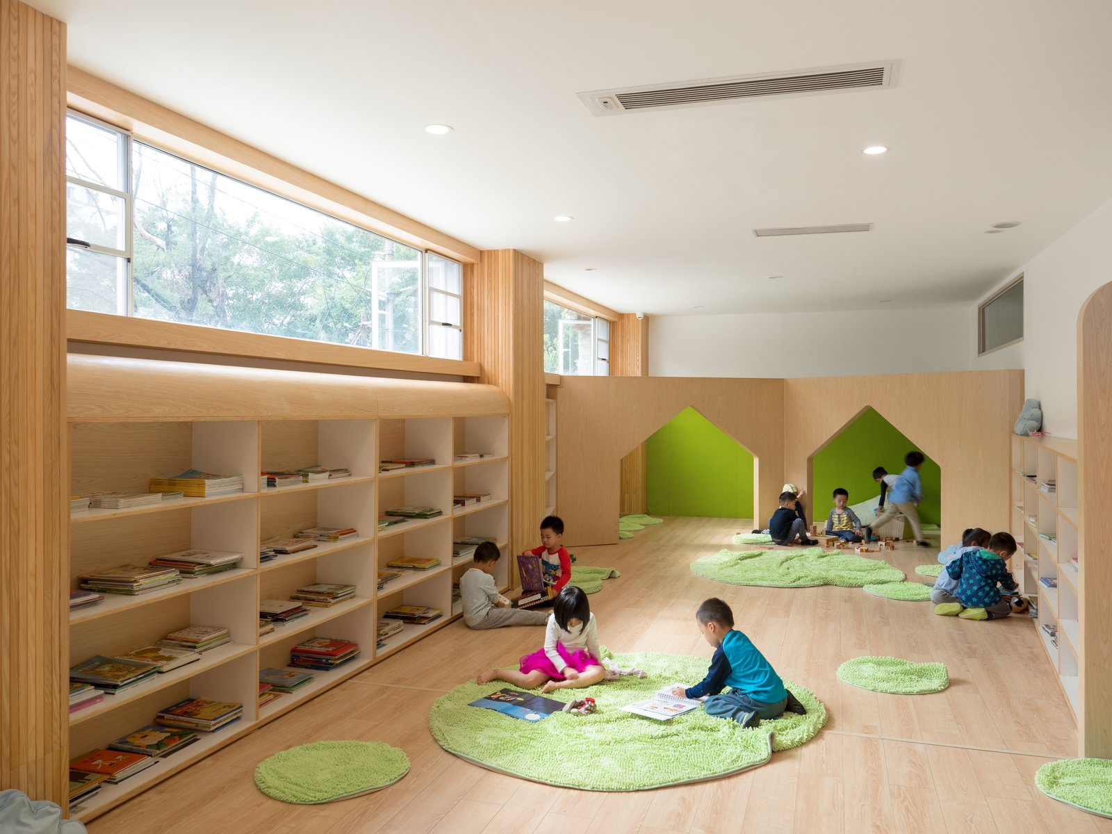 Kids, Toddler, Shelves, Bookcase, Boy, Light Hardwood, Playroom, Living Room, Pre-Teen, Girl, and Neutral Area rugs add warmth to the reading stations.  Kids Bookcase Photos from This Chinese Kindergarten Takes Play Seriously With an Outdoor Climbing Wall