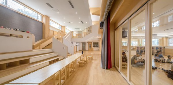 Custom modular furniture and a slide that conjures indoor playground vibes are among the highlights at the sustainably minded Lion International Kindergarten.