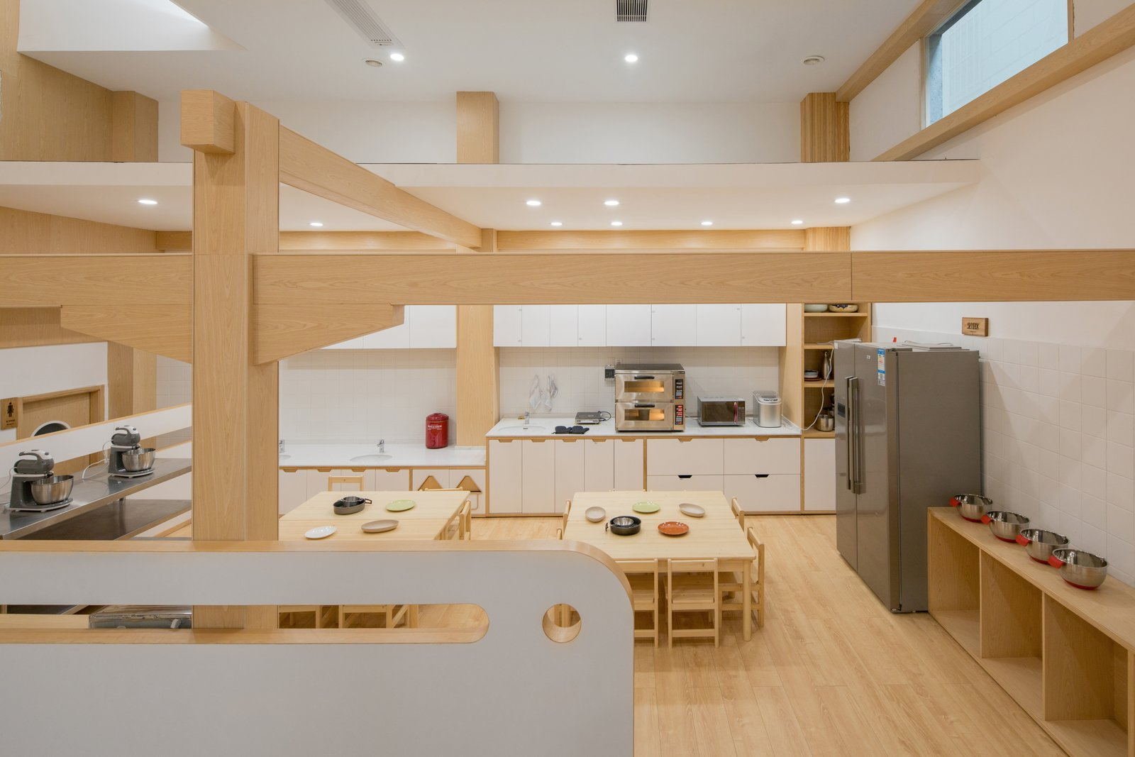 Kitchen, Recessed Lighting, Microwave, Refrigerator, Laminate Counter, Undermount Sink, Light Hardwood Floor, White Cabinet, and Wood Cabinet A cooking classroom contributes to the students' well-rounded education.   Best Photos from This Chinese Kindergarten Takes Play Seriously With an Outdoor Climbing Wall