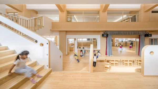Curtains separate the front—where kids dance and partake in carpentry—from the play area in the rear.