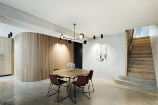 Emphasizing the interior's verticality and curves are the timber walls and screens that enhance spatial flow and light.