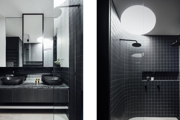 Curved nuances even extend to the shower in the sleek, black-tiled bathroom.