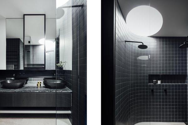 Curved Nuances Even Extend To The Shower In Sleek Black Tiled Bathroom