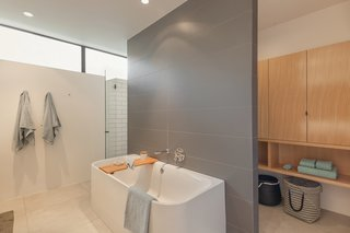 Set against a freestanding wall, the bathtub is a zone of tranquility.