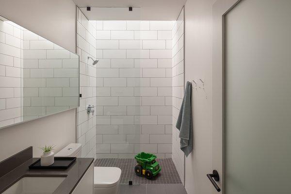 White and gray porcelain La Nova tiles give the bathroom a crisp, contemporary feel.