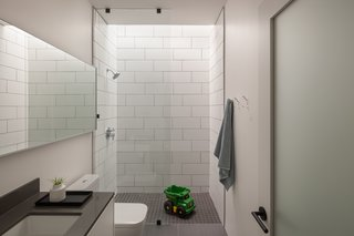 White and gray porcelain La Nova tiles give the bathroom a crisp, contemporary feel.