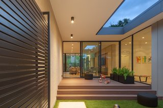 At midcentury-style Pavilion Haus in Houston, the home of StudioMET Architects principal and partner Shawn Gottschalk, Gottschalk ensured that kids could play freely in the contained courtyard while parents kept watch through the sleek glass panels. A large pedestrian gate doubling as the front door establishes a dialogue with nature found throughout the pavilion.