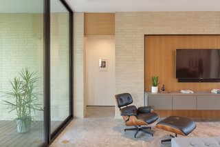 The Eames Lounge Chair in the living area is appealingly positioned by the wall of floor-to-ceiling glass.