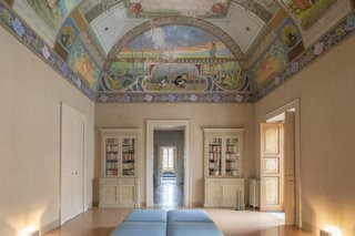 A bright, well-preserved fresco covers the ceiling of the airy common room.