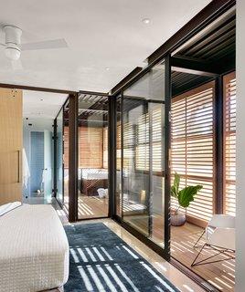 Glass walls bring a sense of brightness to a bedroom and adjacent bathroom.