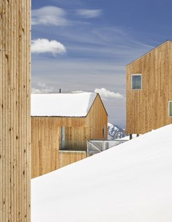 Some cabins follow the mountain's contours while a cross-grain version juts out over the blanket of snow.