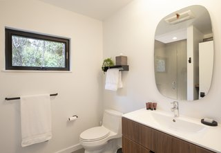 The crisp white bathroom, with a tiled shower enclosed by a glass door.